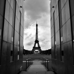 Paris's famous landmark, the Eiffel Tower, seen almost as a silhouette against the cloudy sky. The tower is flanked by the two walls of the Mur de la Paix (Wall of Peace), an art pavilion on the opposite end of the Champs de Mars.
