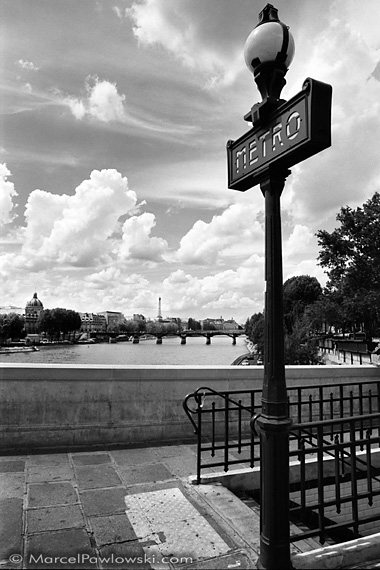 A Metro-sign typical for Paris shot next to the famous and very romantic bridge Pont Neuf over the city's river Seine. The picture even includes the Eiffel Tower in the background.