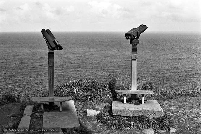Black and white photo of two tourist telescopes overlooking Cap Frehel in Brittanz, France