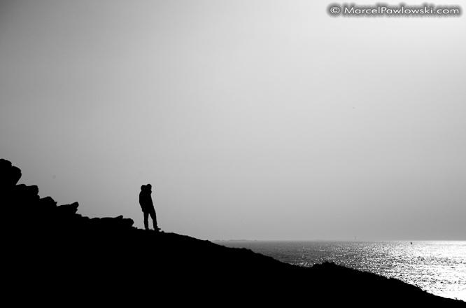 [:en]Silhouette of a single hiker climbing down a cliff at the Phare de Kermorvan[:de]Silhouette eines einsamen Wanderers der eine Klippe beim Phare de Kermorvan herabsteigt.