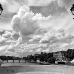 Looking from the Pont Neuf between two lanterns along the Seine, onto the Louvre and the Pont des Arts in front of spectacular clouds in the sky.