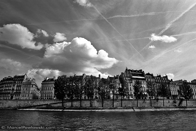 View over the Seine river onto houses and trees along the Quai d'Orleans on the Ile Saint-Louis in Paris.