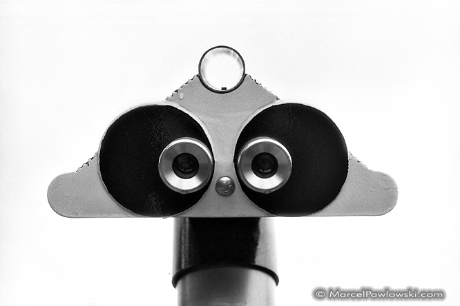 Black and white portrait of a public pay-binocular standing on a hill in the zoo of Karlsruhe, a city in germany.