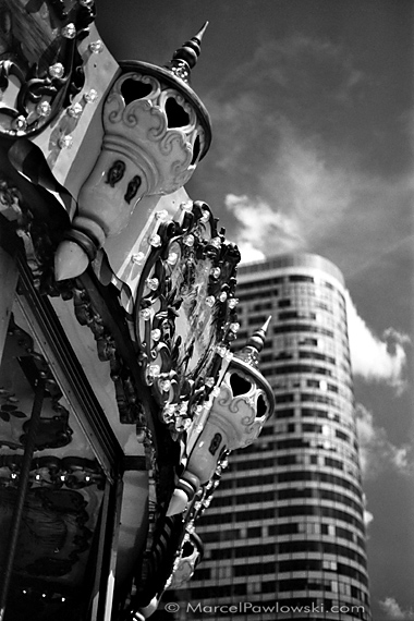 A carousel with playful decor in front of a high-rise building in La Defance, Paris