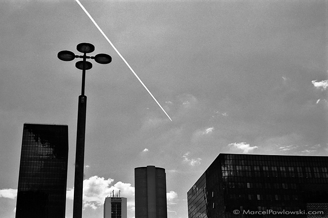 A plane drawing a falling contrail into the sky behind high-rises and a lamp post in La Defance, Paris