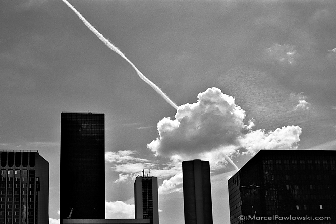 A contrail shooting through a cloud behind the silhouettes of skyscrapers in La Defance, Paris