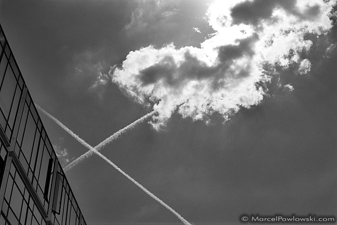 Contrails crossing over a building in La Defance, Paris, next to a cloud lit from behind by the sun.